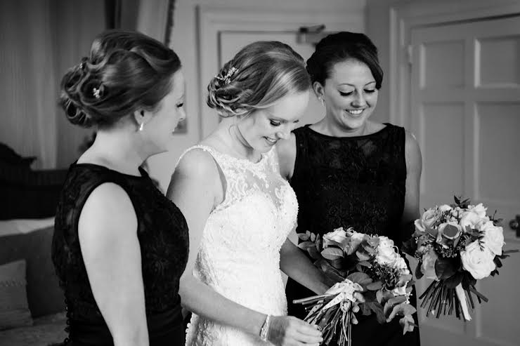 Bride with Bridesmaids, looking at bouquet